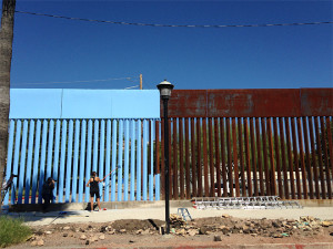 "Artist Ana Teresa Fernandez paints the Sonora border fence blue to ""lower the sky"" as part of the art installation, ""Borrando la Frontera,"" or ""Erasing the Border,"" in Nogales, Mexico,Tuesday, Oct. 13, 2015. (AP Photo/Valeria Fernandez)"