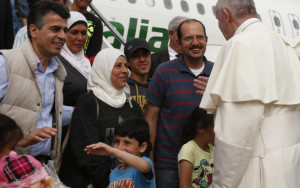 Pope Francis greets Syrian refugees he brought to Rome from the Greek island of Lesbos, at Ciampino airport in Rome April 16, 2016. The pope concluded his one-day visit to Greece by bringing 12 Syrian refugees to Italy aboard his flight. (CNS photo/Paul Haring) See POPE-LESBOS-FLIGHT April 16, 2016.